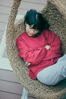 Azjatycki nastolatek śpi w ptasie gniazdo huśtawka na tarasie domu
