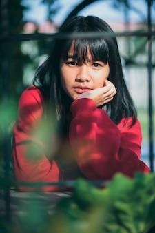 Azjatycki nastolatek ubrany w czerwony sweter siedzi na zewnątrz