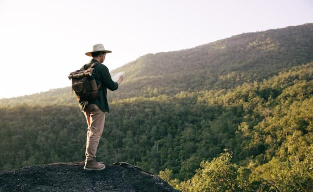 Azjatycki nastolatek używa kompasu z mapą paoer do wędrówki przez las na szczyt góry.