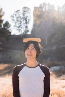 Azjatycki nastolatek zabawy z książką