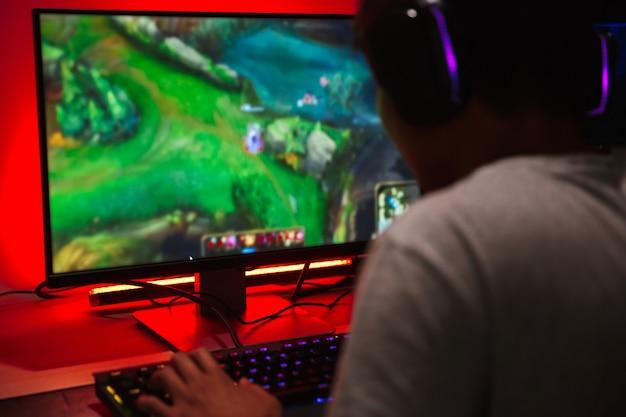 Azjatycki nastoletni chłopiec gamer, grając w gry wideo na komputerze w ciemnym pokoju, nosząc słuchawki i używając podświetlanej klawiatury kolorowej