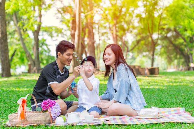 Azjatycki nastoletni rodzinny jeden dzieciaka szczęśliwy wakacyjny pykniczny moment w parku