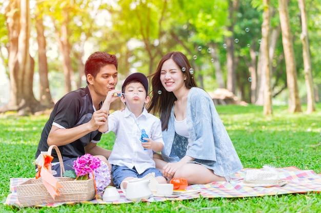 Azjatycki nastoletni rodzinny szczęśliwy wakacyjny pykniczny moment w parku