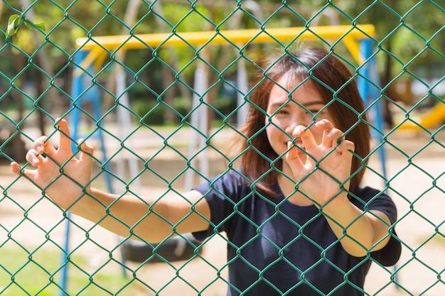 Azjatycki nastoletni uśmiech behide drucianego ogrodzenia