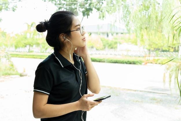 Azjatycki nastoletni z szkłami słucha muzykę na telefonie komórkowym.