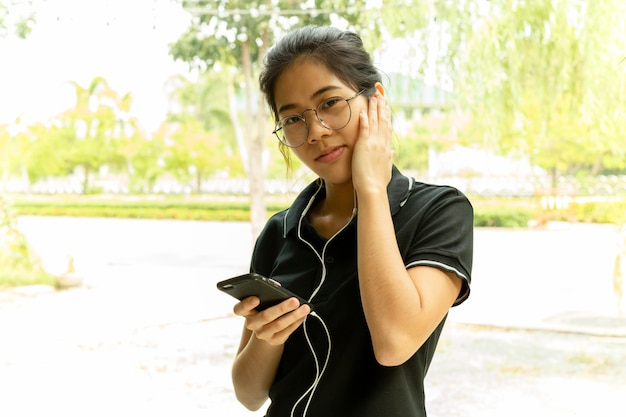 Azjatycki nastoletni z szkłami słucha na telefonie komórkowym patrzeje kamerę.