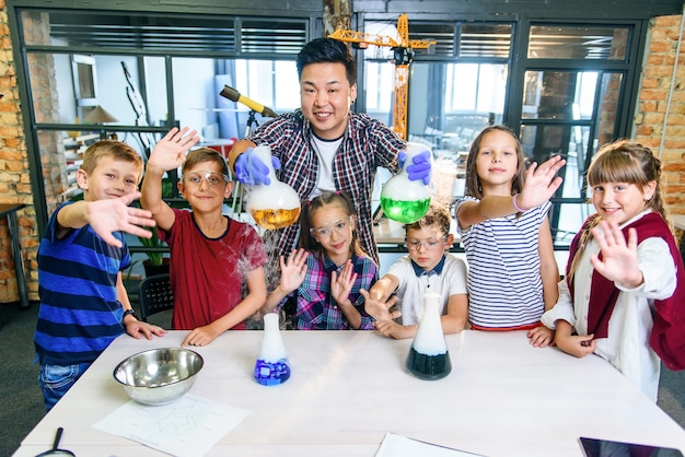Azjatycki nauczyciel robi eksperymenty z suchym lodem dla dzieci w klasie w nowoczesnej szkole. podczas eksperymentu naukowiec trzyma kolbę z dymem reakcyjnym i zabarwioną cieczą.