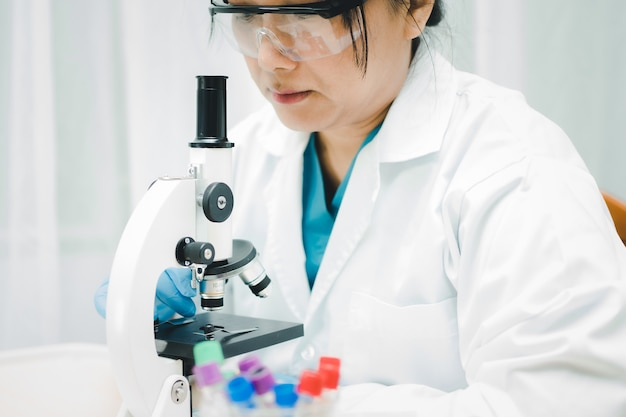 Azjatycki naukowiec biochemik pracuje nad mikroskopem w laboratorium w celu ochrony koronawirusa covid-19.