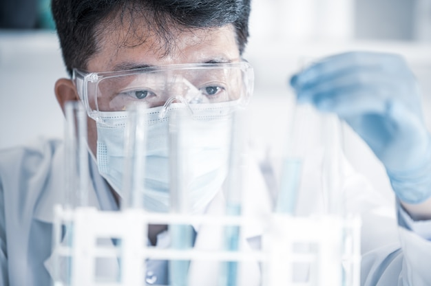 Azjatycki naukowiec płci męskiej pracujący w laboratorium. koncepcja rozwoju szczepionki.