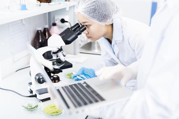 Azjatycki naukowiec używa mikroskop