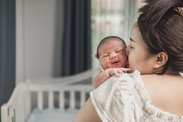 Azjatycki noworodek z matką na łóżku. mama trzyma i całuje swoje dziecko.