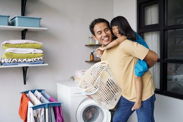 Azjatycki ojciec gra na świnkę razem z córką podczas prania za pomocą pralki