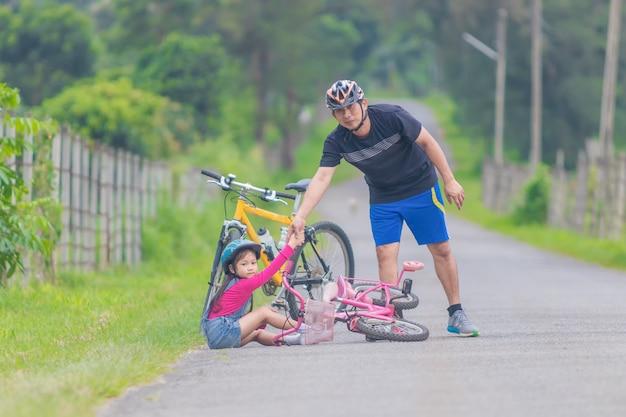 Azjatycki ojciec i córka jeździeccy bicykle na ulicie.