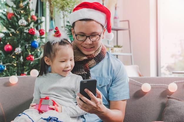 Azjatycki ojciec i córka używa smartphone wpólnie uśmiechająca się twarz w pokoju z choinki dekoracją dla wakacyjnego tła rodzinny przyjęcie gwiazdkowe i świętowania pojęcie.