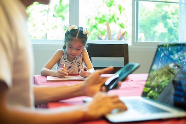 Azjatycki ojciec i jej córka używają komputera i telefonu komórkowego do spotkań i łączenia się online