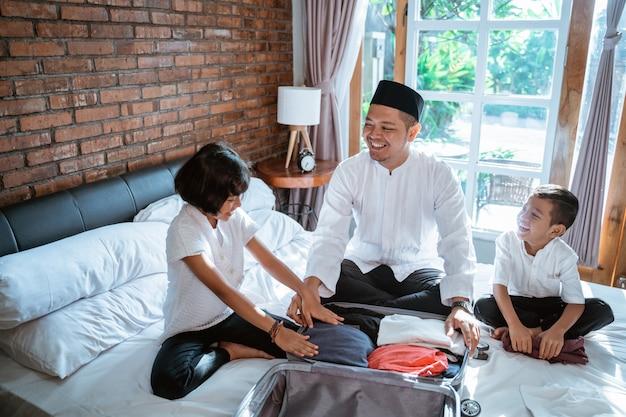 Azjatycki ojciec i jej dziecko przygotowują ubrania i wkładają walizkę do noszenia