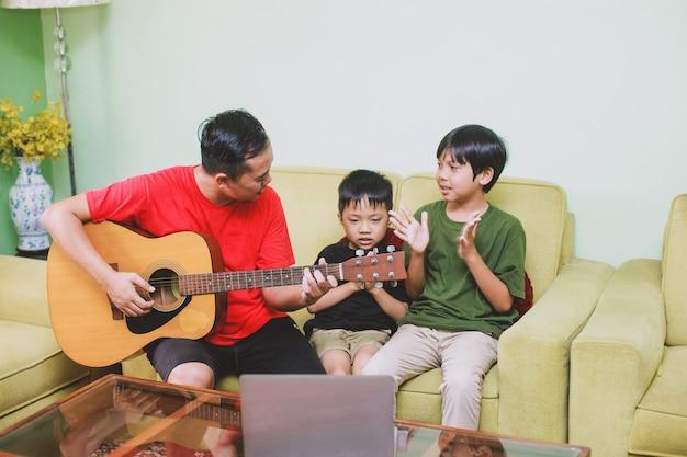 Azjatycki ojciec i syn grają na gitarze i śpiewają razem z synem w domu