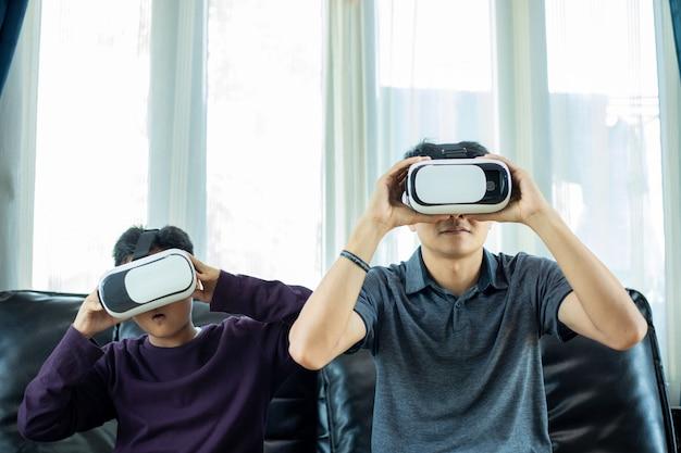 Azjatycki ojciec i syn lubią grać w gry wideo razem z joystickiem wideo i okularami wirtualnej rzeczywistości z ekscytującą i bardzo zabawną zabawą w salonie w domu