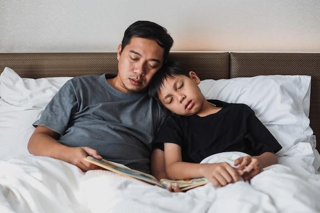 Azjatycki ojciec i syn śpią na łóżku podczas czytania książki