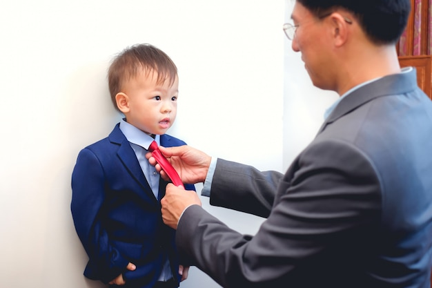 Azjatycki ojciec i syn ubrani w garnitury