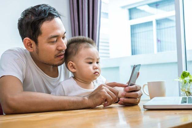 Azjatycki ojciec i syn używa mądrze telefon wpólnie w domowym tle.