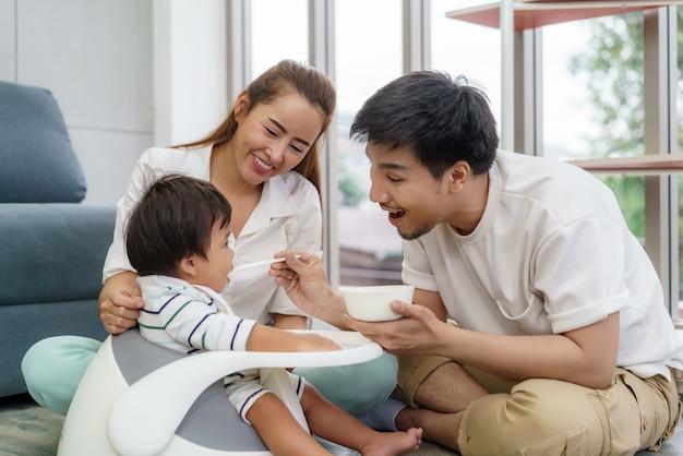 Azjatycki ojciec karmi swojego 6-miesięcznego chłopca stałym pokarmem z łyżeczką i matką siedzącą obok, aby dopingować syna do jedzenia w salonie w domu.