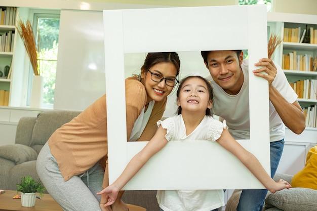 Azjatycki ojciec, matka i jego córka robią zdjęcie z białą ramką, aby zachować dobrą pamięć