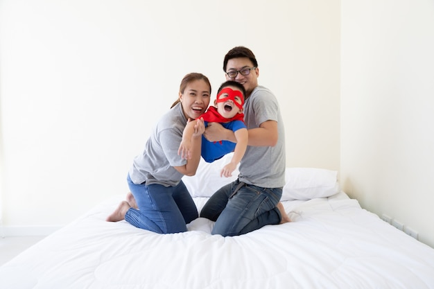 Azjatycki ojciec, matka i syn bawią się w superbohatera na łóżku w sypialni. przyjazna rodzina zabawy