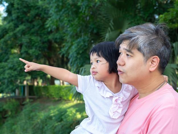 Azjatycki ojciec nosi uroczą córkę na klatkę piersiową. córka wskazuje na to, co widzi.