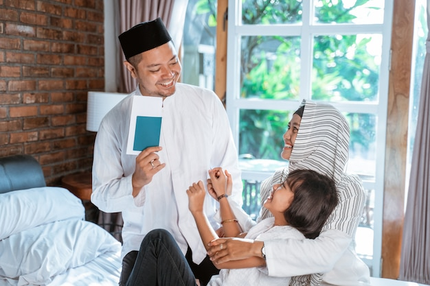 Azjatycki ojciec posiadający paszport, gdy członkowie rodziny przygotowują walizkę do noszenia, gdy mudik