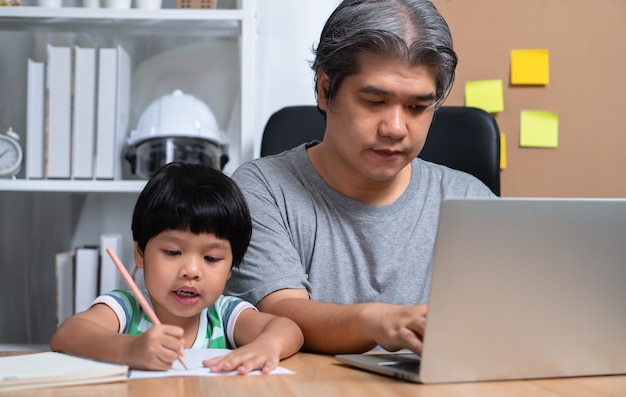 Azjatycki ojciec pracuje z córką w domu i razem uczy się w szkole