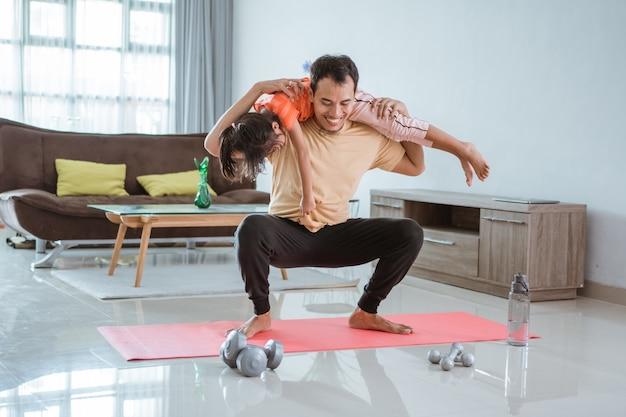 Azjatycki ojciec używa swojego dziecka jako ciężaru do ćwiczeń w domu. mężczyzna robi przysiad, niosąc córkę