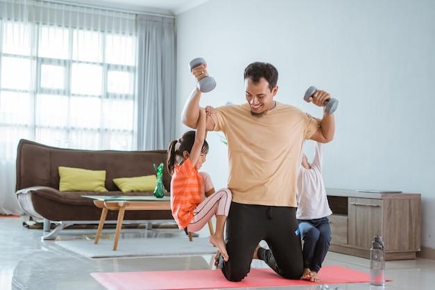 Azjatycki ojciec używa swojego dziecka jako ciężaru do ćwiczeń w domu