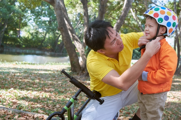 Azjatycki ojciec włożył hełm na uroczego małego 3-letniego malucha chłopca, tatę i syna bawiących się rowerem równowagi (bieg na rowerze) na łonie natury w parku