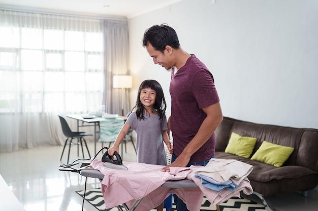 Azjatycki ojciec z córeczką do prasowania ubrań w domu