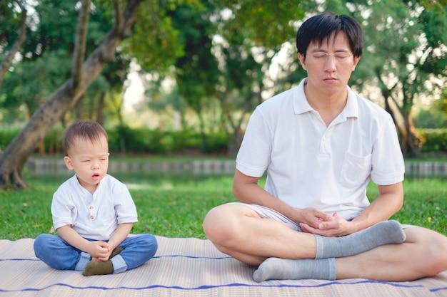 Azjatycki ojciec z oczami zamykającymi i 1 roczniak berbecia chłopiec dzieckiem ćwiczy joga & medytować outdoors na naturze w lecie, zdrowy stylu życia pojęcie