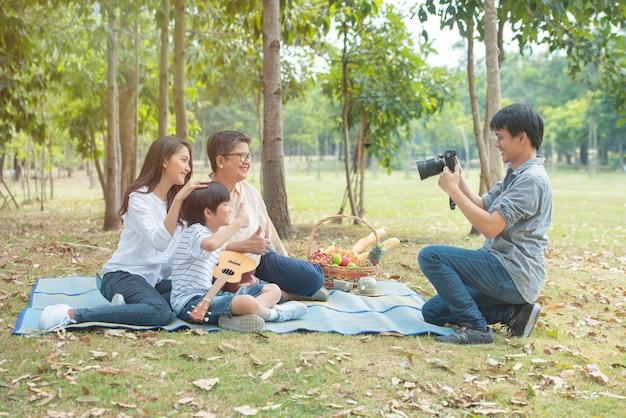 Azjatycki ojciec za pomocą cyfrowego aparatu fotograficznego robi zdjęcie grupowe swojej żony, syna i babci w publicznym parku, happy razem z azji rodziny spędzają wolny czas w weekend.