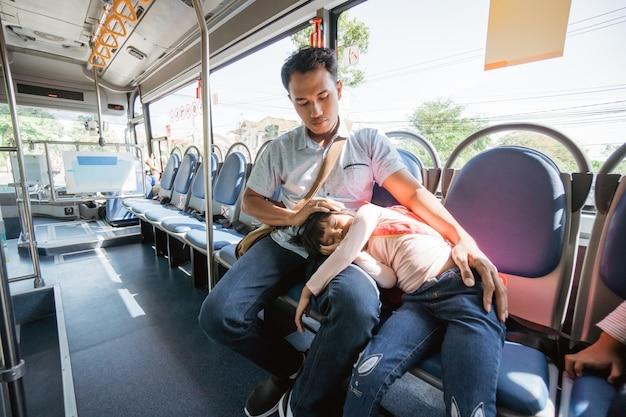 Azjatycki ojciec zabiera córkę do szkoły jadąc autobusem komunikacją miejską