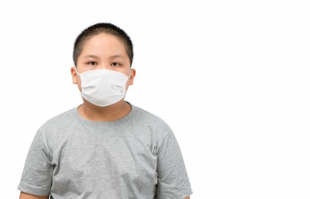 Azjatycki otyły chłopiec ubrany w maskę ochronną w celu ochrony przed epidemią koronawirusa