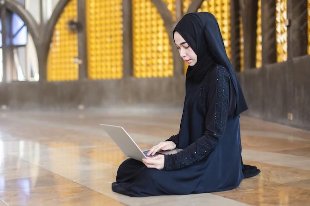 Azjatycki piękny muzułmanin ma na sobie czarne hidżab kobiety pracujące przy użyciu komputera przenośnego, pracy online w odległości i pracy w domu. święta, czasy ramadanu.