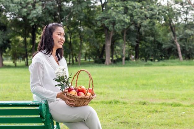 Azjatycki piękny portret starsza kobieta z owocowym koszem i kwiatem w parku.