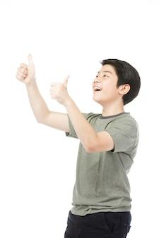 Azjatycki podekscytowany chłopiec w zielonej koszuli daje kciuk w górę.