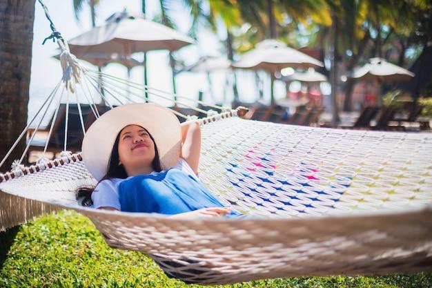 Azjatycki podróżnik kobieta siedzi na hamaku w tropikalnym kurorcie