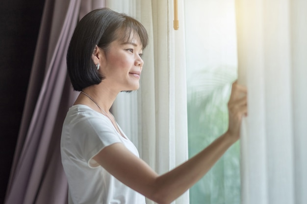 Azjatycki podróżnik kobieta uśmiech i patrząc na zewnątrz w pokoju ze światłem słonecznym