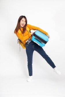 Azjatycki podróżnik kobieta z plecakiem stojąc i trzymając walizki na białym tle.