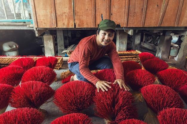 Azjatycki podróżnik, który robi tradycyjne wietnamskie czerwone kadzidło w starym tradycyjnym domu