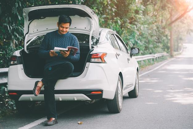 Azjatycki podróżnik siedzi i czyta książkę z otwartym bagażnikiem samochodu
