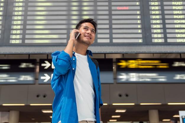 Azjatycki podróżnik sprawdza lot informaci ekran w nowożytnym lotnisku