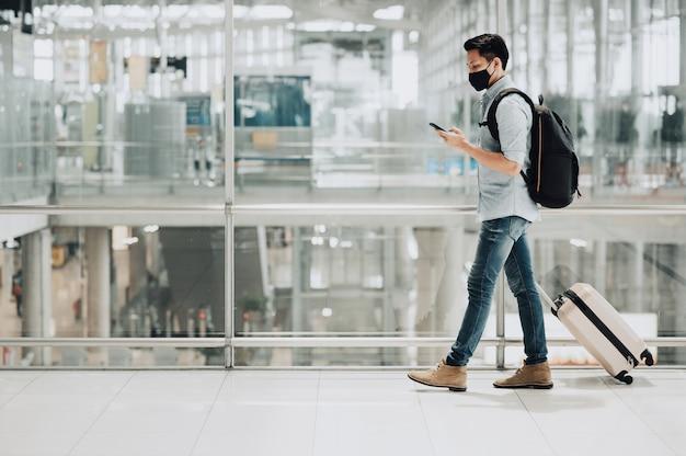 Azjatycki podróżnik w masce w celu ochrony przed koronawirusem trzymający smartfon z bagażem