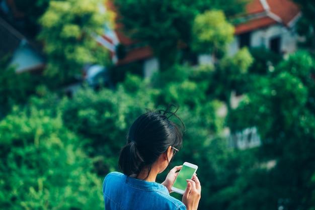 Azjatycki podróżnik w widoku od tyłu używał inteligentnego telefonu